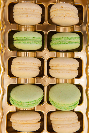 Traditional french sweets macarons in a golden box. Sweet dessert