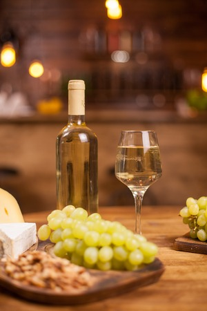 Bottle of white wine a glass full of it next to different cheeses. Fresh grapes. Tasty walnuts. Standard-Bild