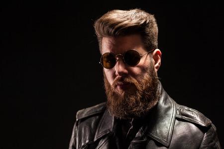 Hombre barbudo elegante con chaqueta de cuero y gafas de sol sobre fondo negro. Hombre rockero. Hombre atractivo.