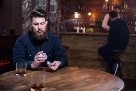 Handsome bearded man lost on his thoughts next to a glass of whisky. Stylish man. Stylish beard. Stock Photo