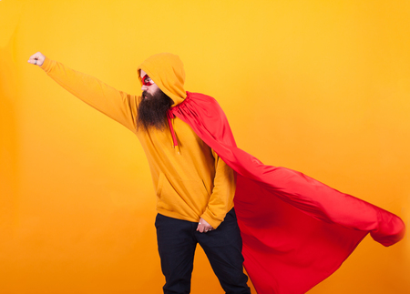 Bearded hipster dressed in superhero costume flying away to save the world over yellow background. Stock Photo