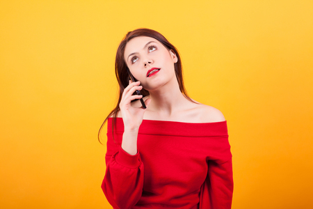 Portrait of beautiful young woman bored while talking on the phone over yellow background
