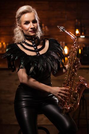 Belle jeune talentueuse jouant du jazz sur son saxophone dans un pub vintage. Concert de jazz. Femme musicienne.