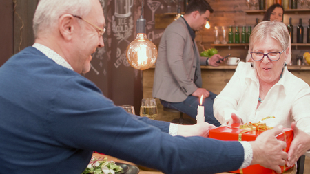Couple in their sixties feeling good in a restaurant. Man giving his wife a gift box. Happy couple. Cheerful senior couple.