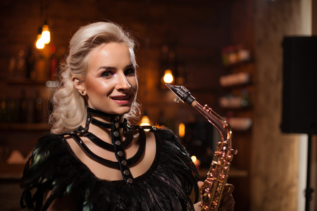 Attractive blonde woman having a jazz concert on her saxopone in a pub