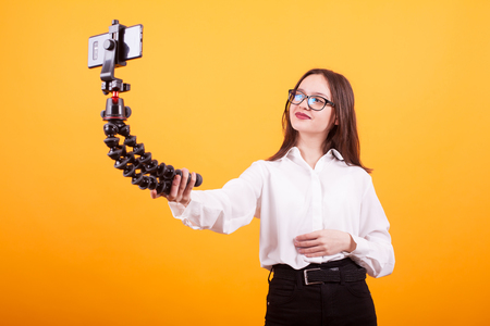 Beautiful young blogger girl taking a selfie in studio over yellow Reklamní fotografie