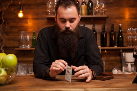 Bearded hipster bartender playing with his trick cards.