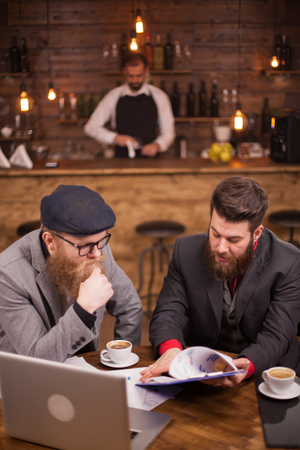 Young managers checking documents of his pub with barman blurred in the background. Succesful men. Stylish bearded men.