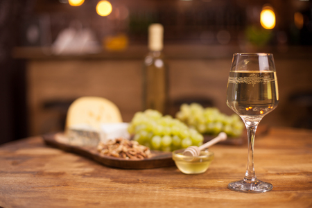 Glass of white wine with super consisting french cheese next to walnuts on rustic wooden table. Food tasting. Fresh grapes. Standard-Bild