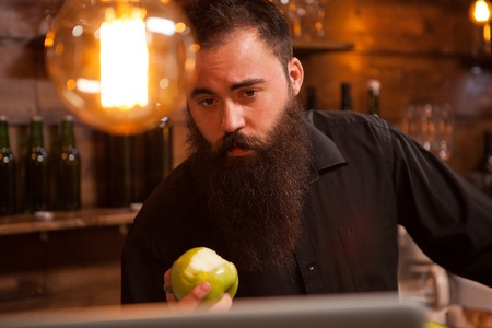 Bearderd bartender eating a green apple in vintage pub