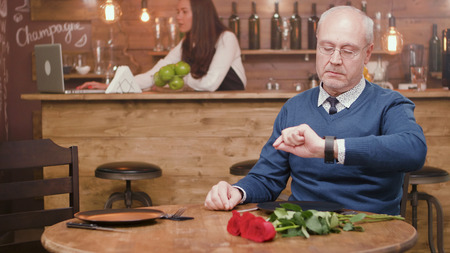 Senior man checking his watch in a restaurant with flower on the table. Relaxed man. Mature man. Stock Photo
