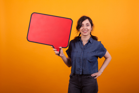 Portrait of young woman holding red thought bubble over yellow background in studio. Cheerful woman with banner in her hand.