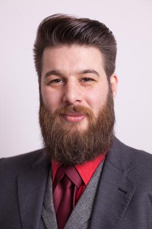 Studioporträt des gutaussehenden bärtigen Mannes über weißem Hintergrund. Stilvoller Bart. Schöner Mann.
