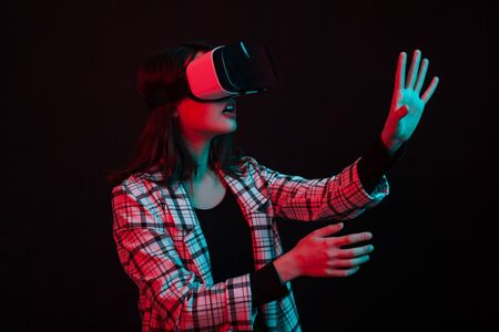 Young girl wearing virtual reality goggles headset in studio with colorful lighting. Futuristic virtual reality goggles.