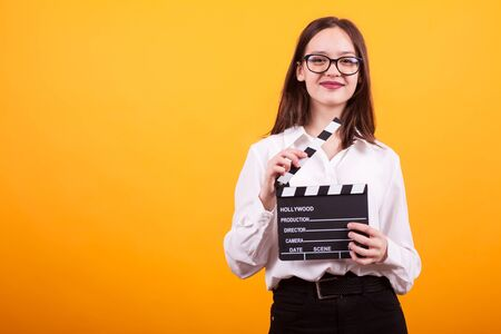 Pretty young girl with cinema board holding it in her hands and smiling to the camera in studio over yellow background. Cheerful teenage girl with eyeglasses standing with cinematography board in hands.