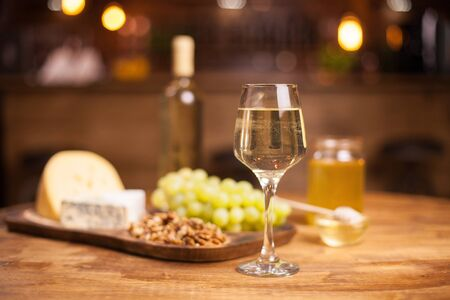 Photo of a sparkling white wine on a rustic wooden table in a vintage pub. Tasty cheese. Delicious grapes. Walnuts.
