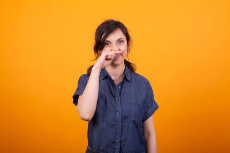 Portrait of funny young woman scratching her nose after using cosmetics.