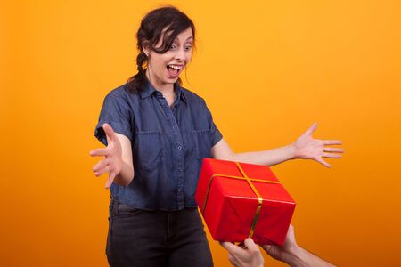 Portrait of cheerful young woman when seeing a red gift box in studio over yellow