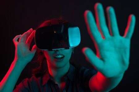 Attractive young woman adjusting her virtual reality goggles in studio with colored lighting. Young female using modern gadget.