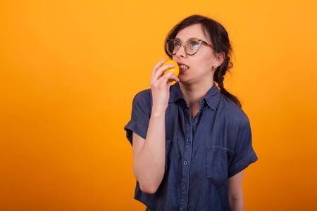 Portrait of cute young woman freaked out with orange in her hand over yellow background in studio. Girl with delicious orange.
