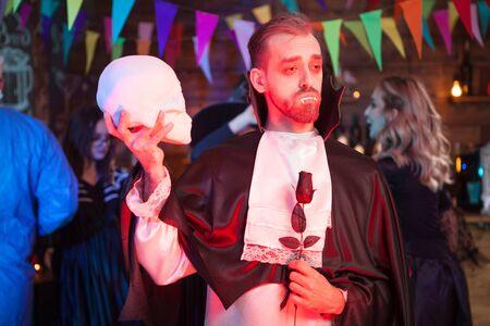 Gut aussehender Mann gekleidet in einem Dracula-Kostüm für Halloween. Mann, der Halloween feiert.