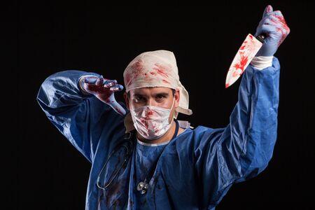 Jeune homme habillé comme un médecin atteint de schizophrénie pour le carnaval d'halloween. Docteur maniaque avec couteau couvert de sang.