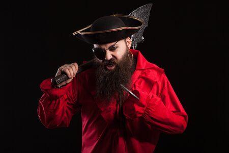 Porträt eines mittelalterlichen bärtigen Piraten auf schwarzem Hintergrund. Männlicher Pirat mit einem aggressiven und ernsten Ausdruck. Standard-Bild