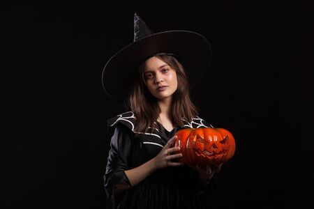 Little girl with a serious expression making a spell while holding a pumpking for halloween. Child dressed up for halloween carnaval.