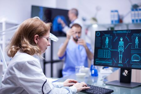 Woman working with computer in the office of a science laboratory. Male scientist working with test tubes in the background. Фото со стока
