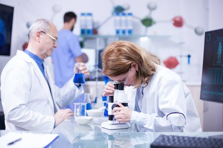 Ältere Wissenschaftlerin, die in einem Labor gegen Krankheiten arbeitet. Senior männlicher Wissenschaftler mit einem Reagenzglas in der Hand. Standard-Bild