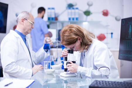 Senior vrouwelijke wetenschapper werkzaam in een laboratorium tegen ziekten. Senior mannelijke wetenschapper met een reageerbuis in zijn hand. Stockfoto
