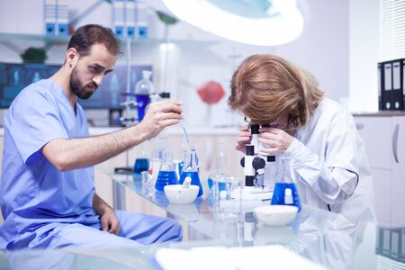 Joven científico masculino caucásico con una pipeta analiza un líquido para extraer moléculas en tubo de ensayo. Microscopio de ajuste científico de sexo femenino. Foto de archivo
