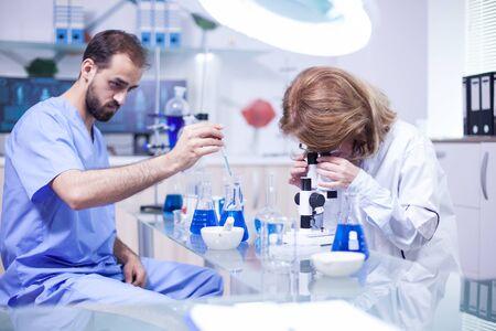 Młody naukowiec rasy kaukaskiej mężczyzna za pomocą pipety analizuje ciecz, aby wyodrębnić cząsteczki w probówce. Kobieta naukowiec regulacji mikroskopu. Zdjęcie Seryjne