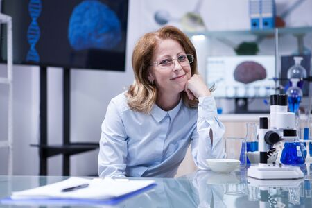 Portrait of middle age scientist thinking about her career at her office in a hospital laboratory. successful scientist.