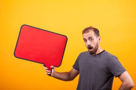 Porträt des überraschten jungen Mannes, der die Kamera betrachtet und ein Nachrichtenbrett über gelbem Hintergrund hält. Exemplar vorhanden.