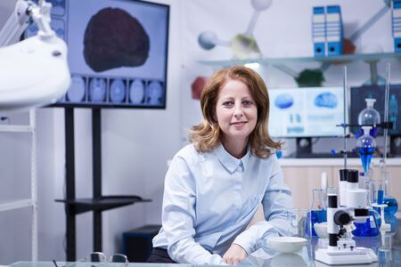 Portrait of middle age woman in a scientist laboratory. Female technician.