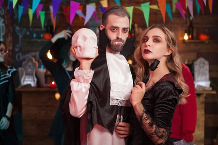 Wounderful couple in halloween costumes at a party. Man dressed up like Dracula for halloween celebration.