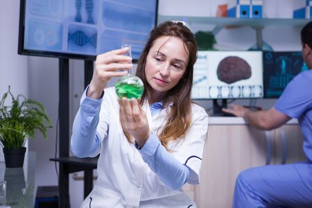 Modern science in a research lab with a middle age female scientist. Young male scientist working in the background.