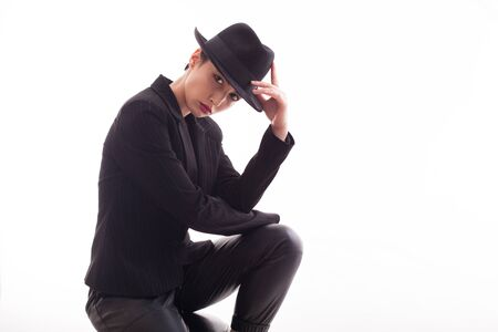 Attractive caucasian female with a stylish hat posing in studio over a white background. Fashion model. Stock Photo