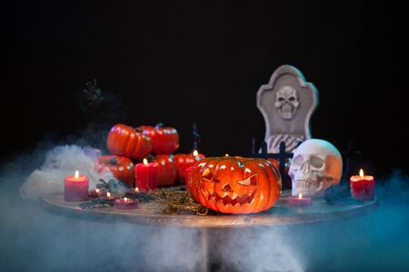 Scary pumpkin and creepy skull sitting together on a wooden table at halloween party. Halloween smoke. Haunted headstone.