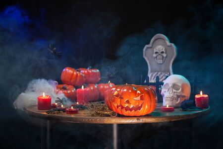 Wooden table with smoke and halloween decoration on it. Spooky carved pumpkin for hallowee party. Stock fotó