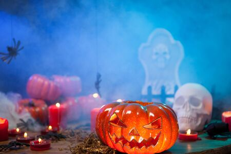 Scary pumpkin for halloween surrounded by mist on a wooden table. Burning candles.