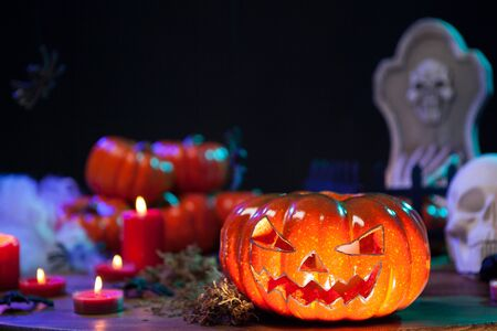 Haunted orange pumpking on halloween celebration. Little pumpkings in the background. Halloween decoration.