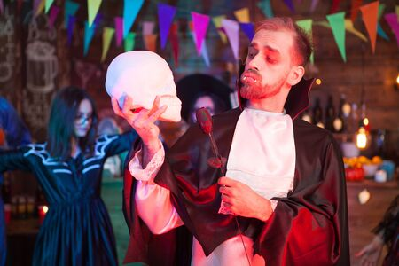 Attractive young man dressed up like dracula holding a black rose looking at his human skull at halloween celebration. Dracula costume.