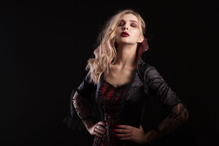 Woman dressed up like a vampire posing for halloween carnival on dark background. Charming woman in dark costume for halloween.