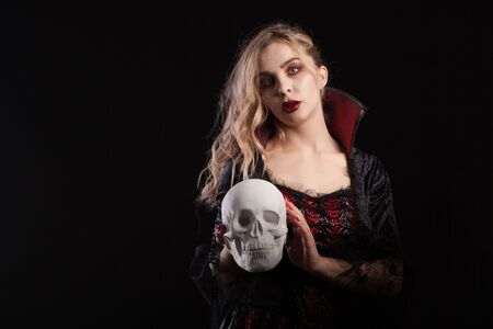 Human skeleton holded by beautiful woman dressed up like a sexy vampire for halloween. Halloween makeup.