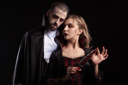 Schöne junge Vampirfrau mit einer mit Blut bedeckten Klinge, die ihren Mann ansieht, der wie Dracula für Halloween verkleidet ist. Verführerisches Paar. Standard-Bild