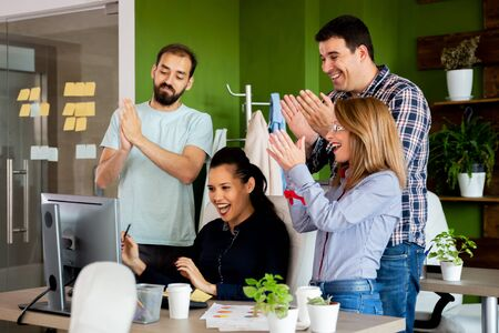 Happy partners in company office clapping in front of computer screen. They received a big news