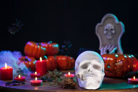 Spooky human skull with scary pumpkin behind on wooden table for halloween celebration. Halloween celebration. Stock fotó