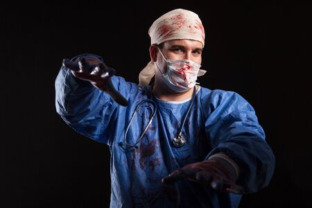 Crazy Doctor with a surgeon mask and scrubs splattered with blood for halloween. Dangerous doctor over black background.